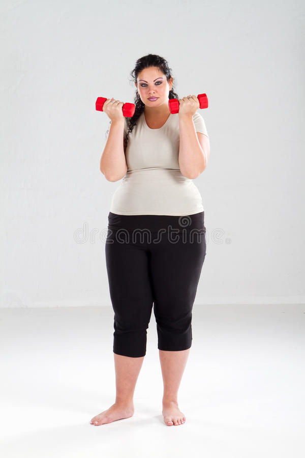 поднимаясь избыточный вес утяжеляет женщину стоковое фото