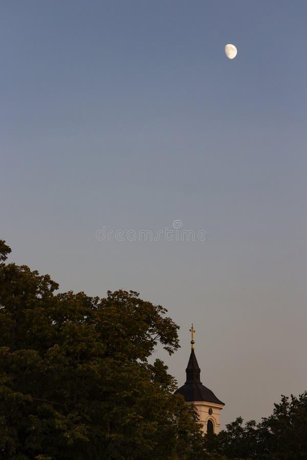 Поднимая луна высоко над башней церков St. George в Kladovo, Сербии стоковое фото