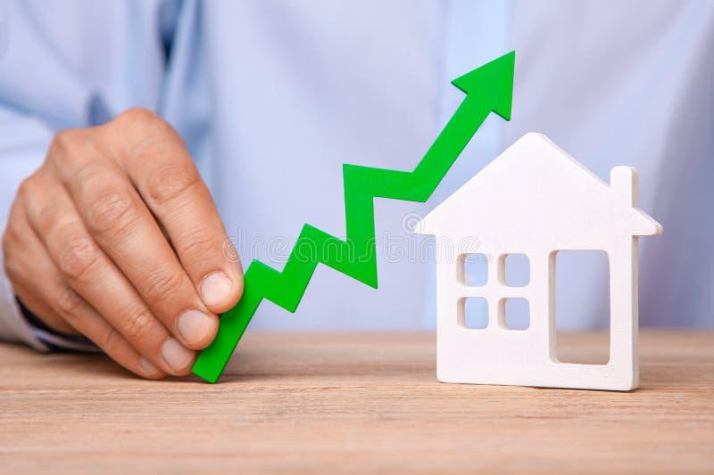 Поднимая цены на дом Человек держит зеленую стрелку вверх в его руке и доме стоковые фото