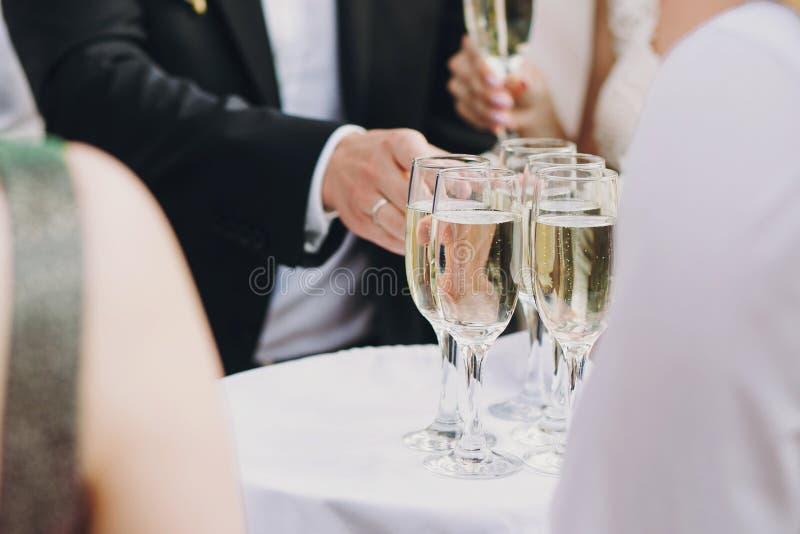 Поднос сервировки официанта со стеклами шампанского для гостей на приеме по случаю бракосочетания outdoors портрет человека стекл стоковые изображения