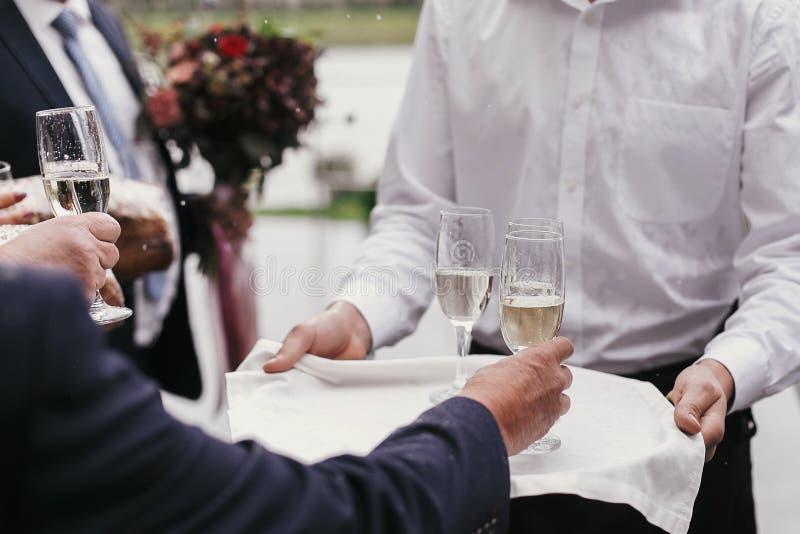 Поднос удерживания официанта со стеклами шампанского и служения им f стоковое изображение rf