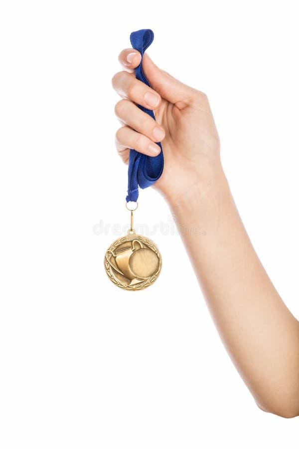 Поднятая рука девушки держащ золотую медаль стоковое изображение