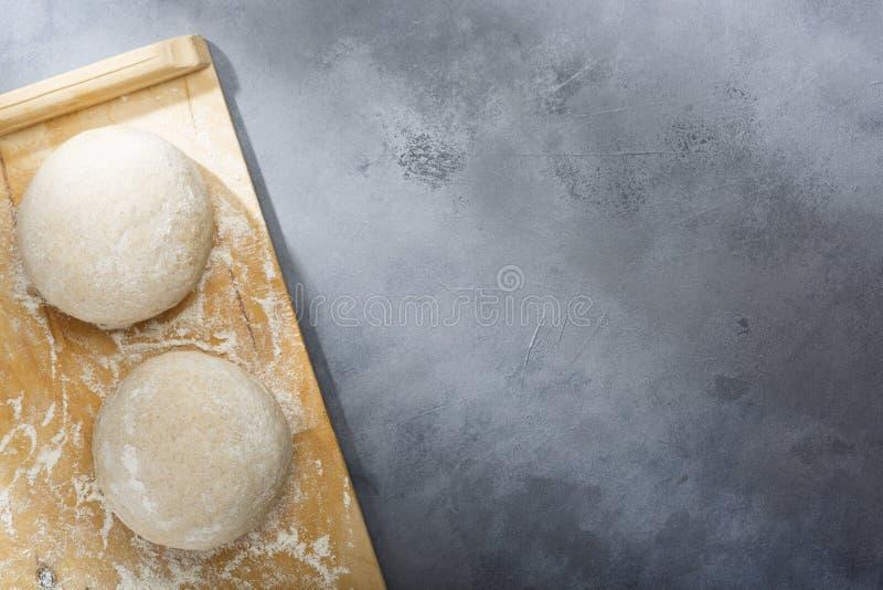 Поднятое или доказанное тесто дрожжей для хлеба или пиццы на floured поверхности шифера стоковое изображение rf
