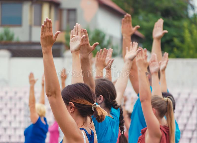 Поднятые руки людей и женщин для тренировки йоги в парке стоковые фото