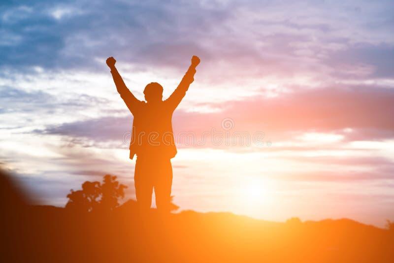 Поднятый человек оружий против красивого захода солнца стоковые фотографии rf