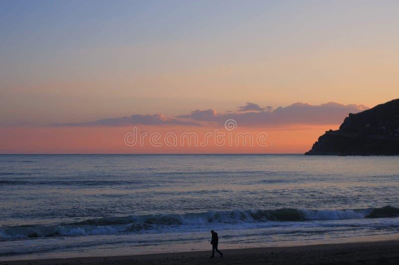 подпирайте Средиземное море, вечер, розовый заход солнца на банке сиротливый человек в городе Alanya горы расстояния видимом стоковые фотографии rf