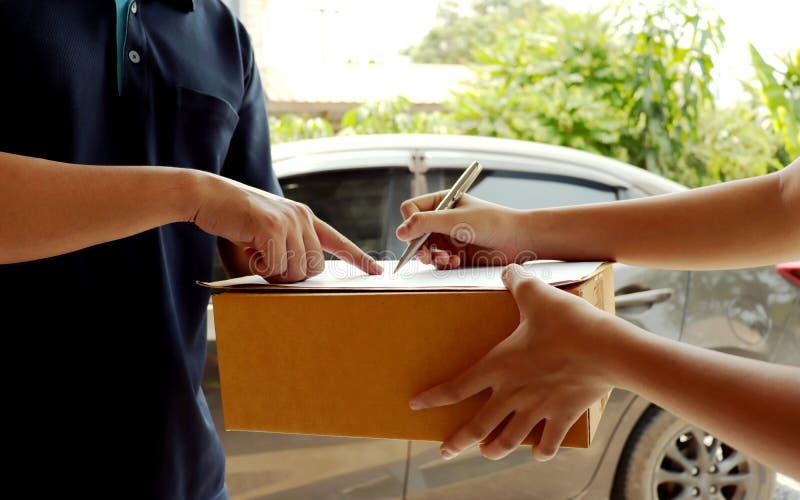 Подписи клиента на доске сзажимом для бумаги для того чтобы получить пакеты от профессионального штата доставки стоковое фото rf