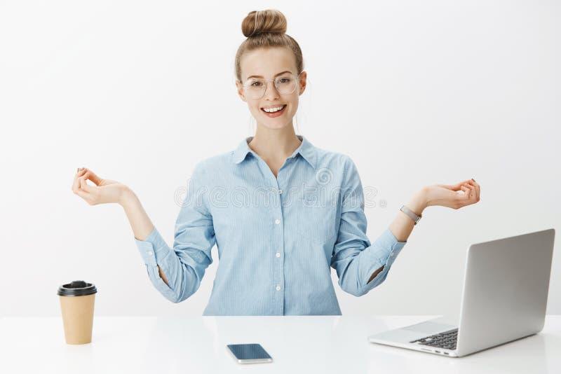 Подпитанный и счастливый молодой творческий женский работник офиса оставаясь положительный как размышлять в офисе около ноутбука  стоковая фотография rf