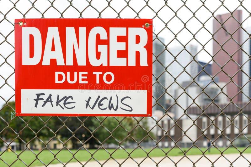 Подпишите опасность должную к поддельной смертной казни через повешение новостей на загородке стоковая фотография rf
