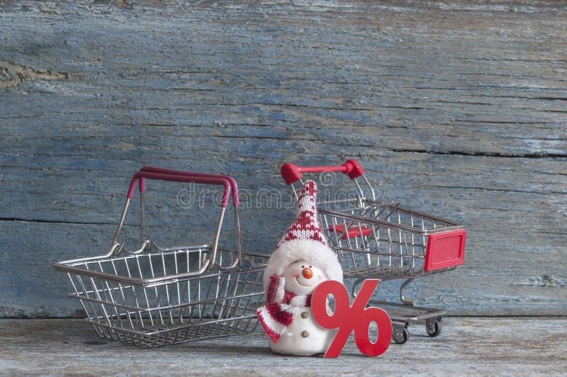 подпишите проценты и магазинную тележкау на деревянной предпосылке стоковые изображения