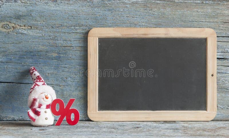 подпишите проценты и милый снеговик на деревянной предпосылке стоковое изображение rf