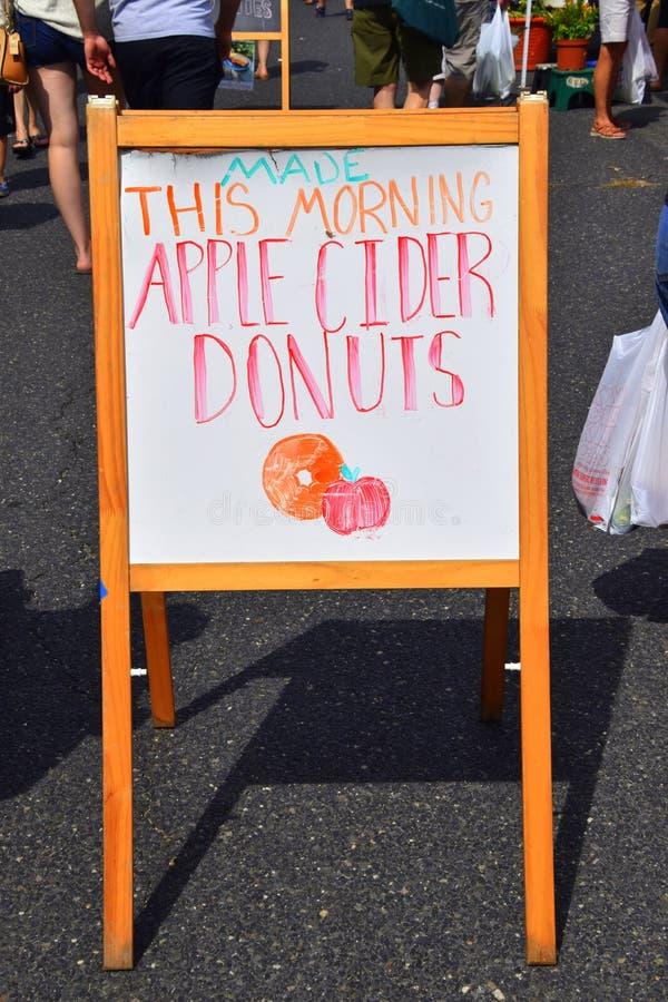 Подпишите рекламировать свежие donuts яблочного сидра с вычерченным изображением яблока и донута стоковые фото