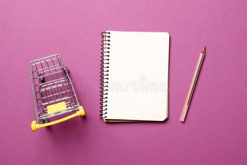Подпрыгивая тележка, тетрадь чистого листа бумаги с ручкой на розовой предпосылке стоковое фото rf