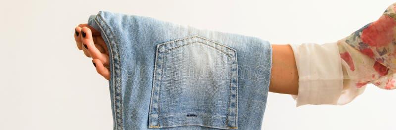 Подрежьте взгляд женской руки держа пару джинсов на белой предпосылке стоковые фотографии rf