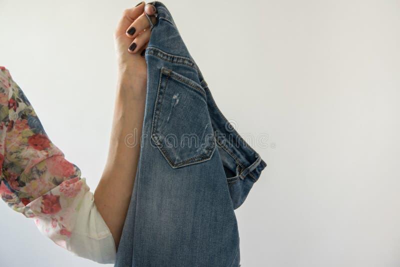 Подрежьте взгляд женской руки держа пару джинсов стоковая фотография