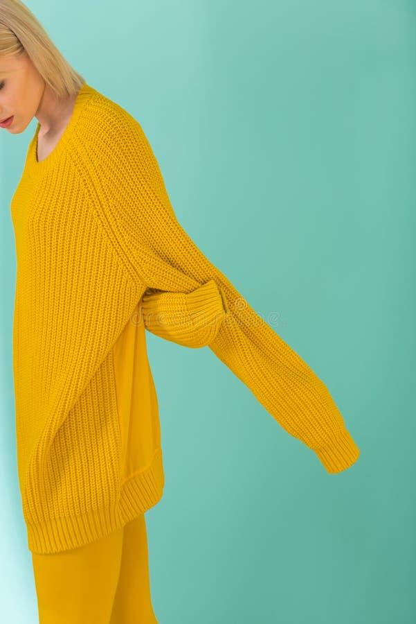подрезанная съемка женщины в желтый представлять свитера стоковое фото