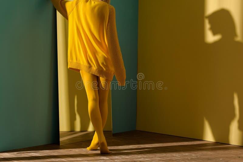 подрезанная съемка женщины в желтый стоять свитера и колготков стоковые фото