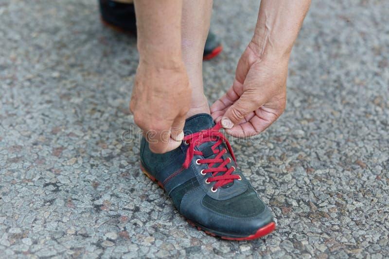Подрезанная съемка зрелых шнурков ботинок хода колготков рук ` s человека, стоек на асфальте перед бегом утра, recreats внешних в стоковая фотография rf