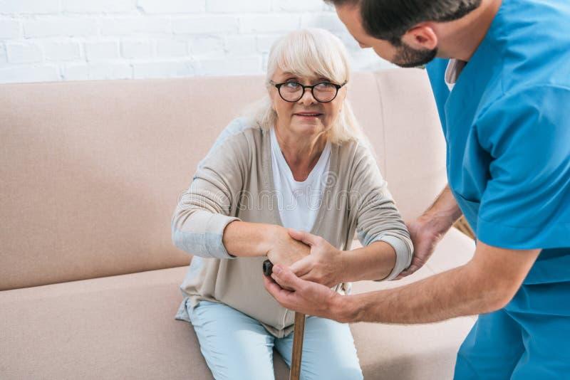 подрезанная съемка мужской медсестры помогая старшей женщине стоковая фотография