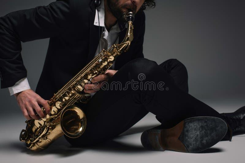 подрезанная съемка музыканта играя саксофон пока сидящ стоковая фотография rf