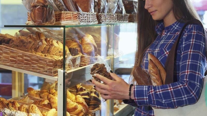 Подрезанная съемка пакета женского клиента рассматривая печений на хлебопекарне стоковые изображения