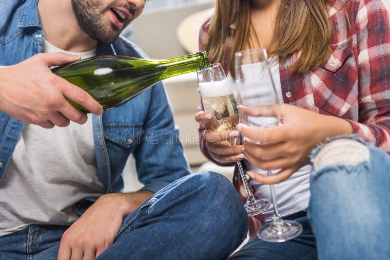 Подрезанная съемка пар сидя на поле дома и лить шампанском стоковые изображения rf