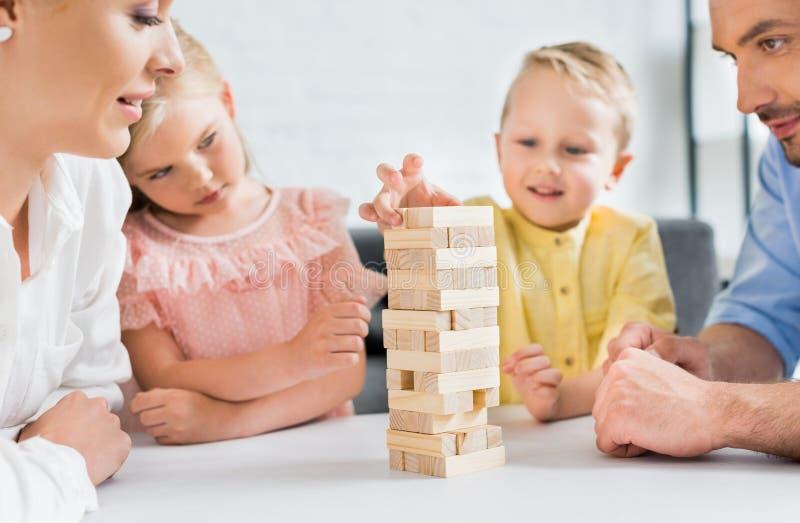 подрезанная съемка родителей смотря милые маленькие ребят играя с деревянными блоками стоковое изображение