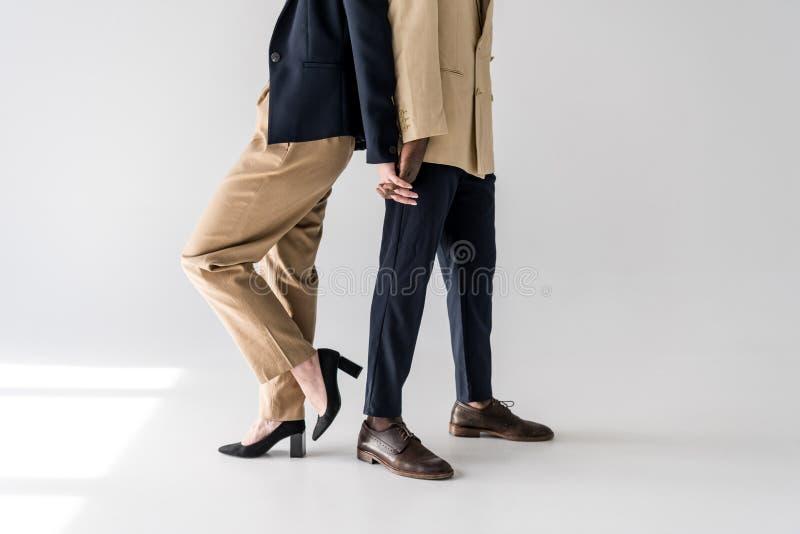 подрезанная съемка стильных молодых многонациональных пар стоя спина к спине и держа руки стоковое изображение rf