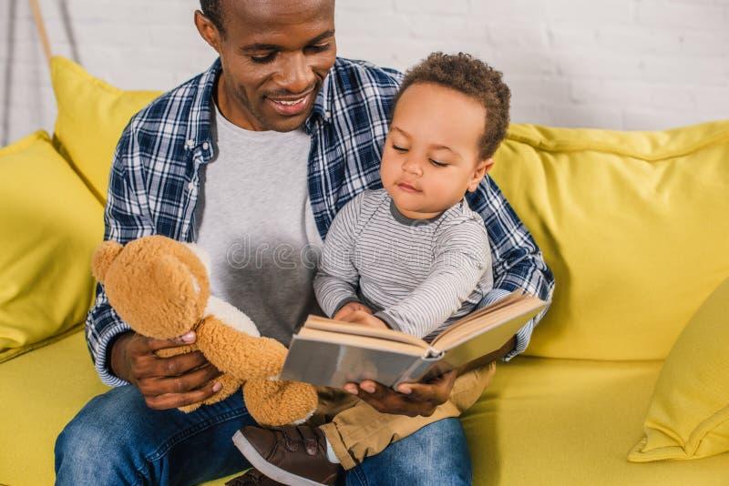 подрезанная съемка усмехаясь плюшевого мишки удерживания отца и книги чтения к стоковое изображение rf