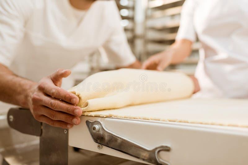 подрезанная съемка хлебопеков свертывая тесто с промышленным роликом теста стоковое фото rf
