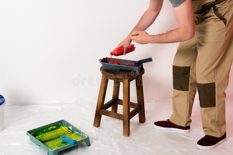 подрезанная съемка человека в работе полно лить краски от бутылки в поднос ролика стоковые изображения rf