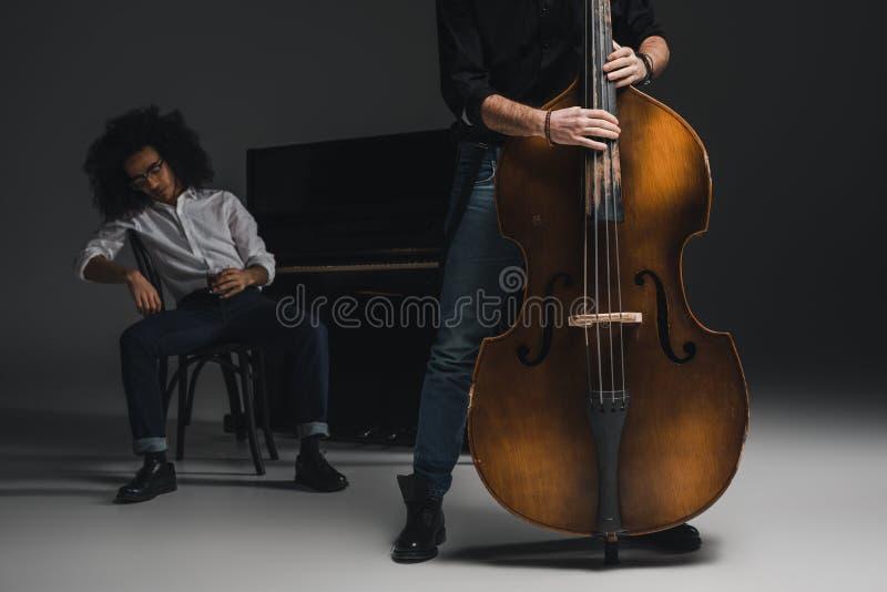 подрезанная съемка человека играя violoncello пока его подавленный партнер сидя на запачканном рояле стоковое фото rf