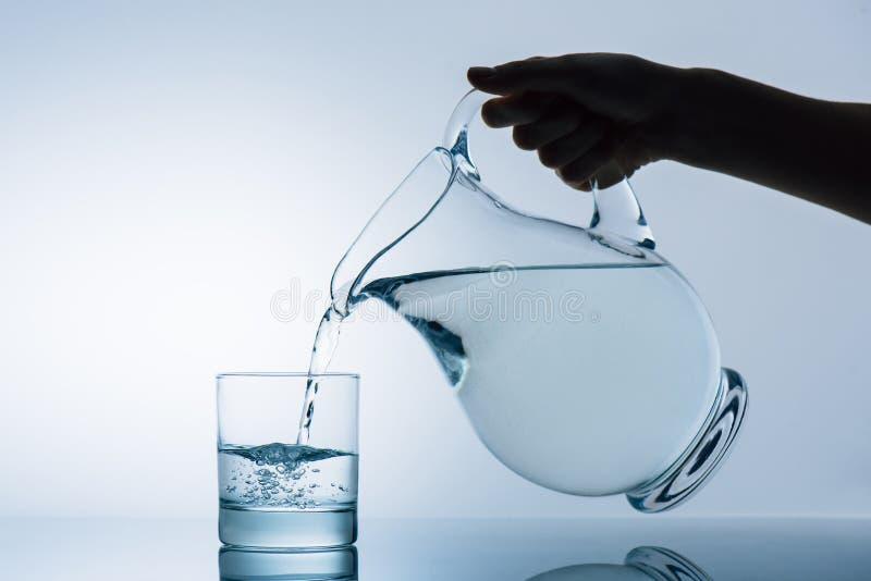 Подрезанное изображение воды женщины лить от прозрачного кувшина стоковые изображения rf