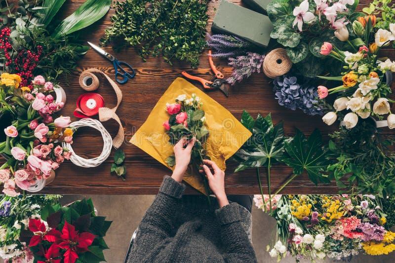 подрезанное изображение женского флориста оборачивая букет стоковые фотографии rf