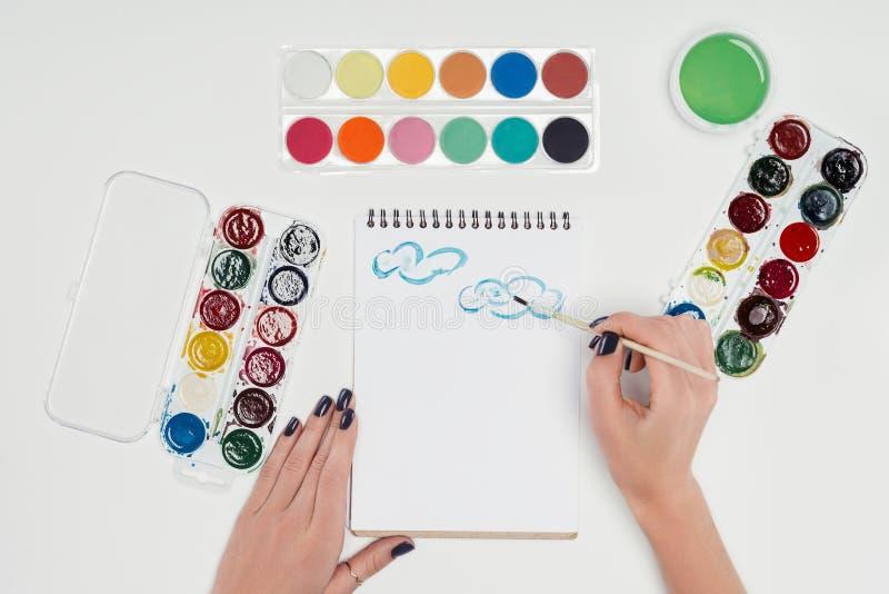подрезанное изображение женского чертежа художника paintbrush в учебнике на белой таблице с красочным стоковые изображения rf