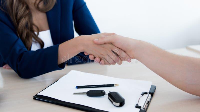 Подрезанное изображение клиента и администраторов по сбыту тряся руки стоковая фотография rf