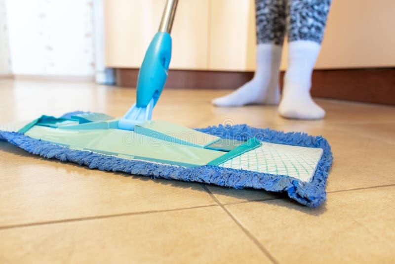Подрезанное изображение красивой молодой женщины используя голубой mop пока очищающ пол в кухне стоковые фото