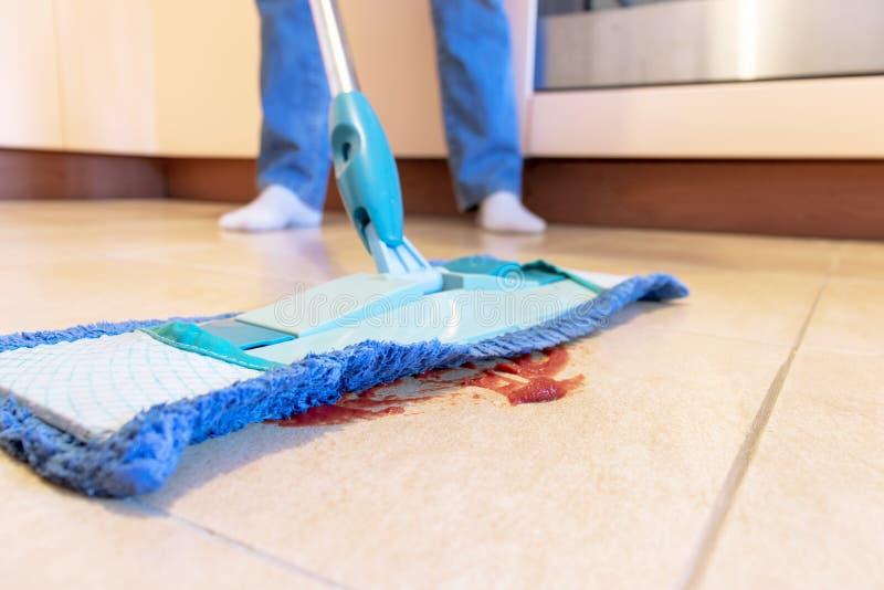 Подрезанное изображение красивой молодой женщины используя голубой mop пока очищающ пол в кухне стоковое фото