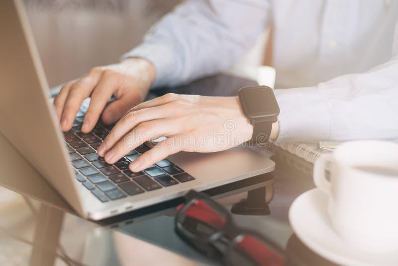 Подрезанное изображение молодого человека работая на его ноутбуке, руки человека занятые использующ ноутбук на столе офиса, молод стоковая фотография