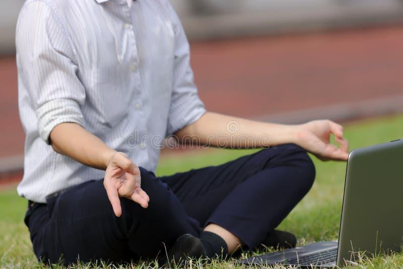 Подрезанное изображение расслабленного молодого азиатского бизнесмена при компьтер-книжка делая положение йоги на зеленой траве стоковые фотографии rf