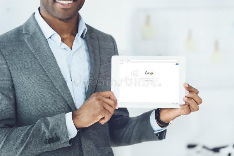 подрезанное изображение усмехаясь Афро-американского человека показывая таблетку с нагруженной страницей Google стоковая фотография rf