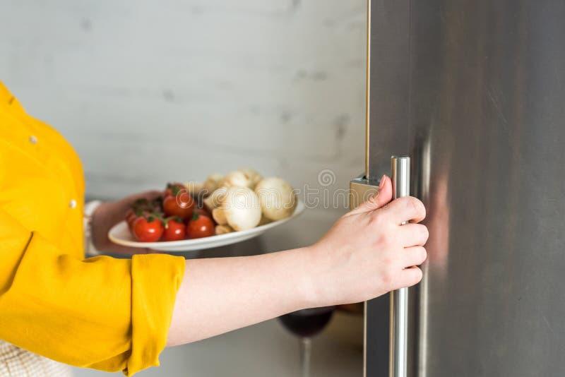 подрезанное изображение холодильника отверстия женщины и плиты удерживания с грибами и томатами стоковое фото rf