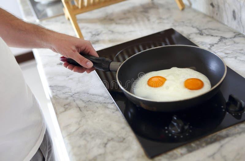 Подрезанное изображение человека варя взбитые яйца на сковороде стоковое фото