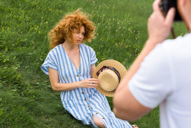 подрезанное изображение человека фотографируя привлекательная женщина redhead с соломенной шляпой стоковые изображения