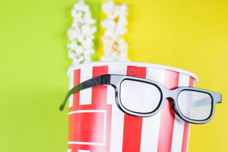 Подрезанное крупным планом фото взгляда бумажной коробки с вкусным попкорном нося черное крутое со спецификациями отражения посту стоковая фотография rf