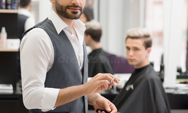 Подрезанное фото парикмахера работая в парикмахерскае используя острые ножницы стоковые изображения
