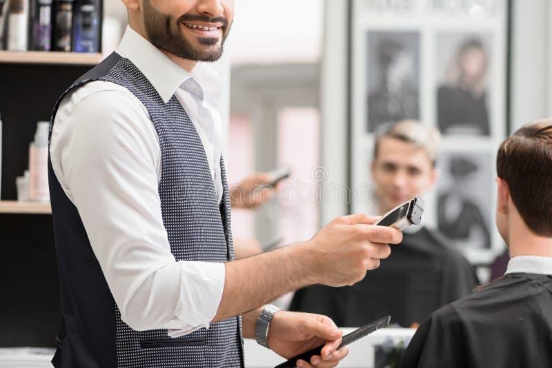 Подрезанное фото усмехаясь парикмахера делая hairdress для клиента в парикмахерскае стоковая фотография