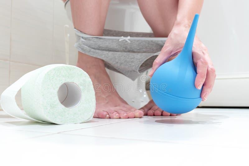 Подрезанные ноги женщины, сидя на туалете с пониженными трусами, голубой очищая клизме в ее руке и крене туалетной бумаги внутри стоковая фотография