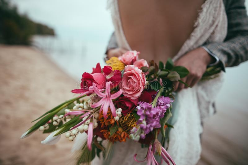 подрезанный взгляд жениха и невеста держа букет и обнимать свадьбы стоковое фото