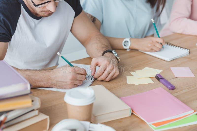 подрезанный взгляд молодых студентов писать в тетрадях с прописями стоковое фото rf